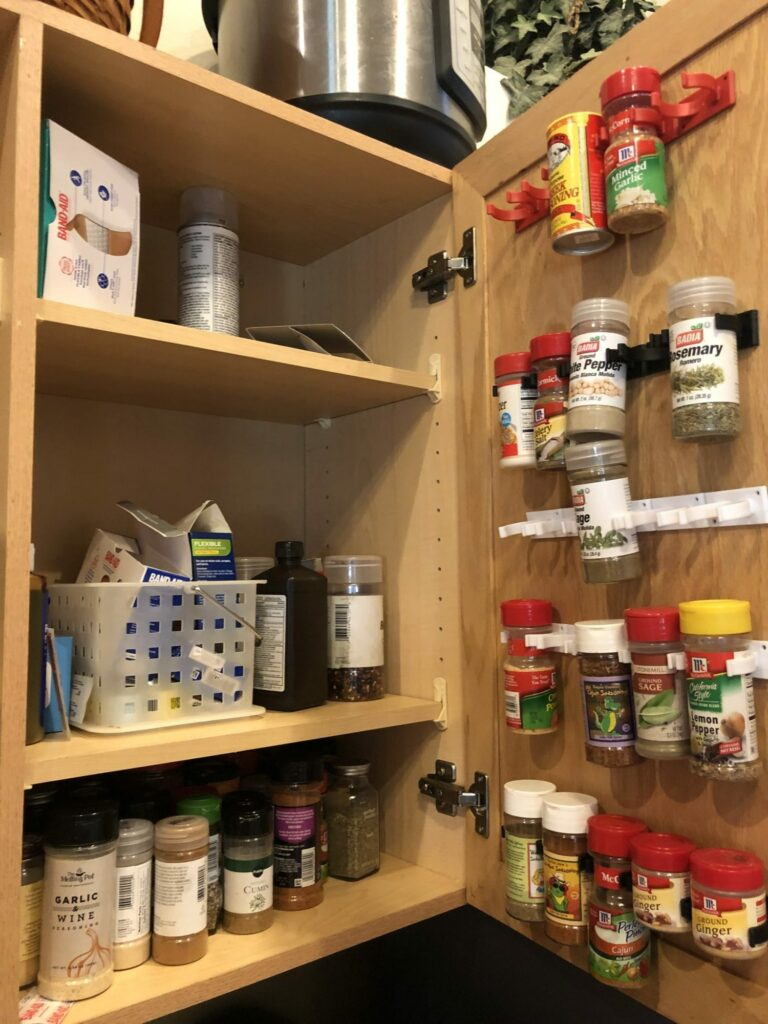 My messy cabinet and spice racks on the door